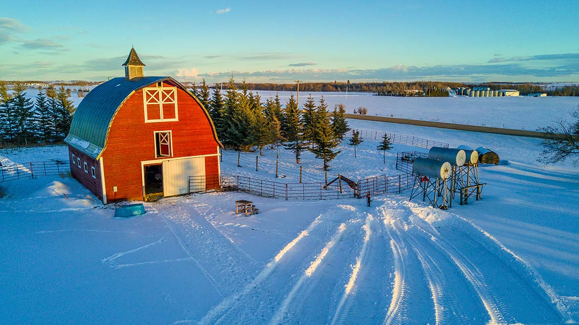 Red barn and corral on a farm in the winter.