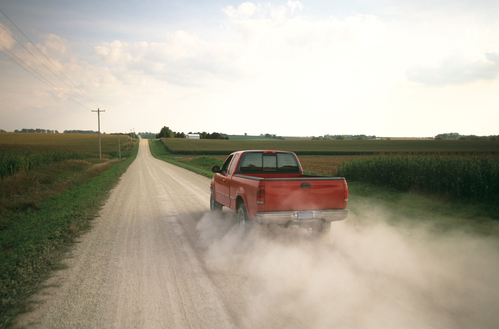 Truck driving down a dusty dirt road in the country.