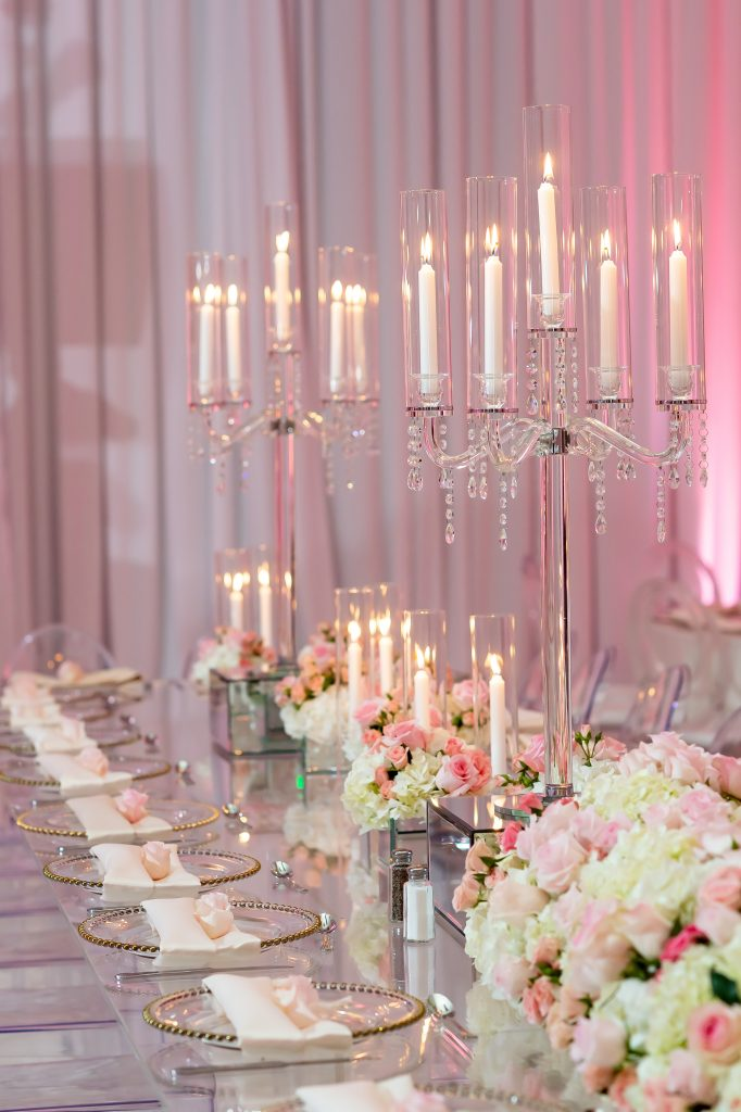 Image of a king's table with clear acrylic plates that have gold rims, and napkins on top. Low floral centerpieces in pink and white flow down the center of the table, and candles on mirrored boxes are interspersed throughout. Two tall candelabras are spaced down the center.