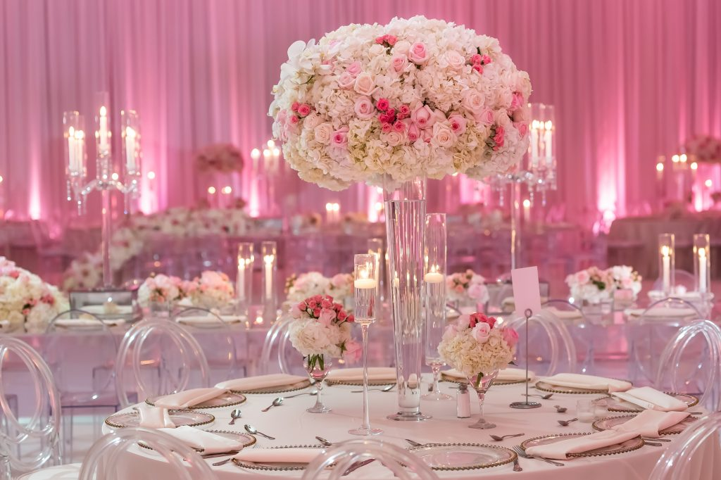 tall floral centerpiece on a tapered vase filled with a large centerpiece. There are small floral arrangements and other candles surrounding the main centerpiece. The table sits in front of a reception hall with other tables in the background with candelabras, and pink uplights on the walls.