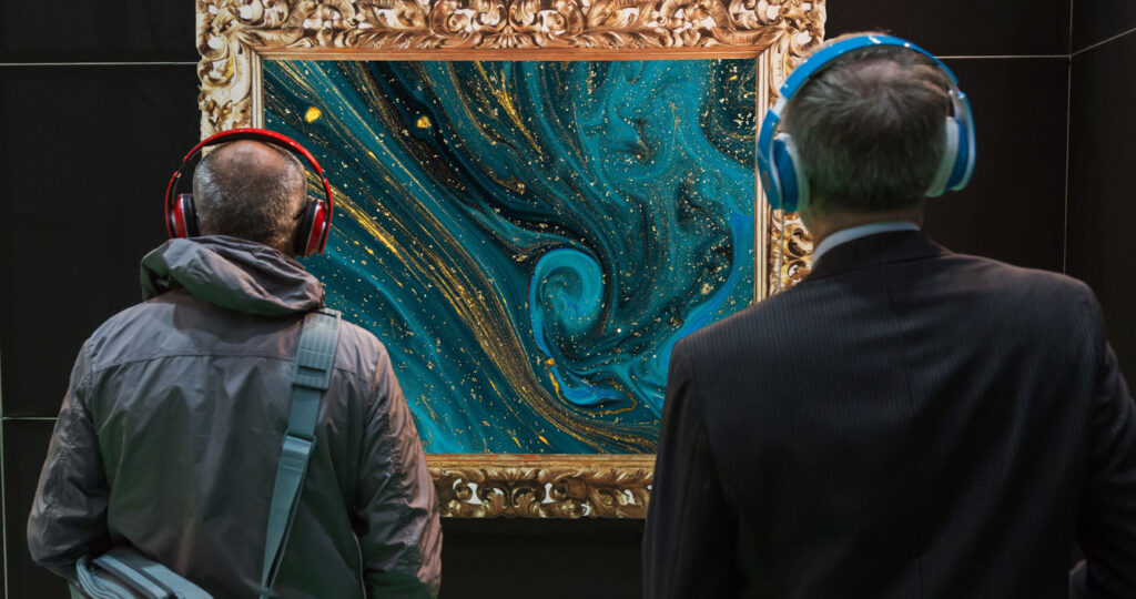 two men wearing headphones looking at a painting of blue and gold swirls