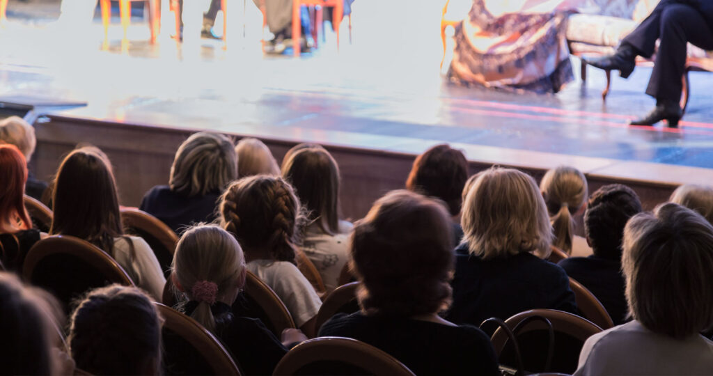 audience and stage with blurry view of actors
