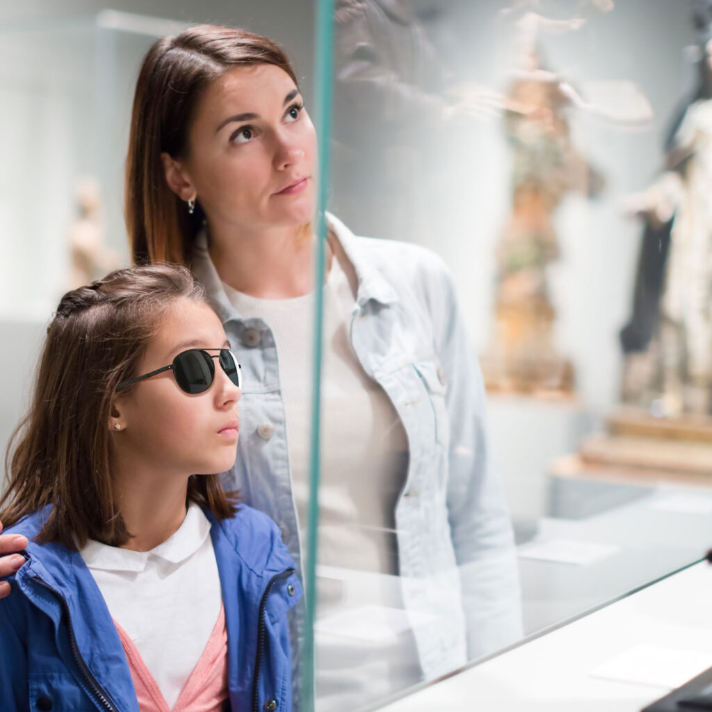 Young woman and child with sunglasses in front of a display