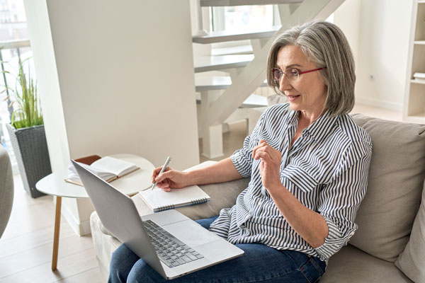 older woman writing notes as she watches a laptop computer