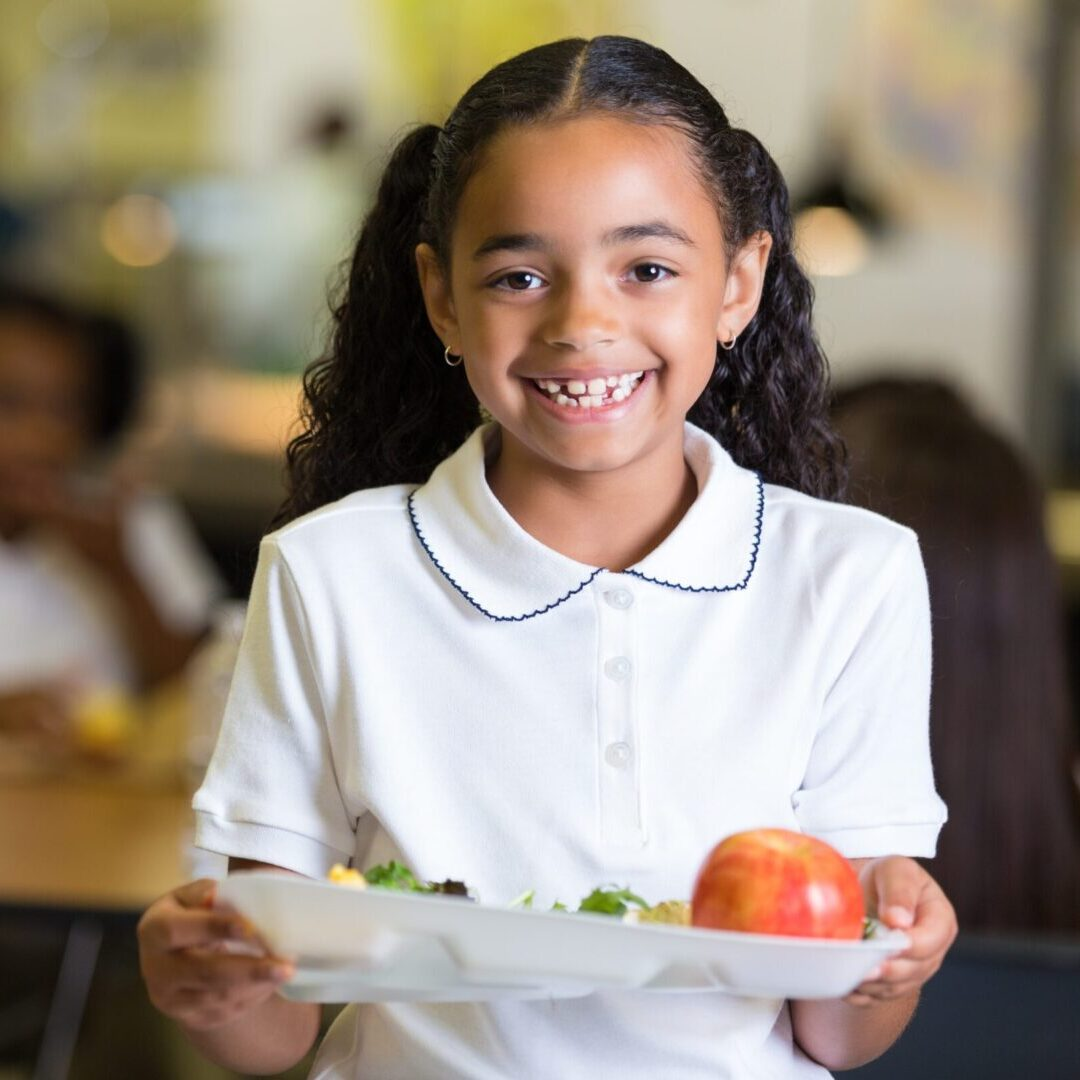 Cute little girl in school cafeteria with food tray