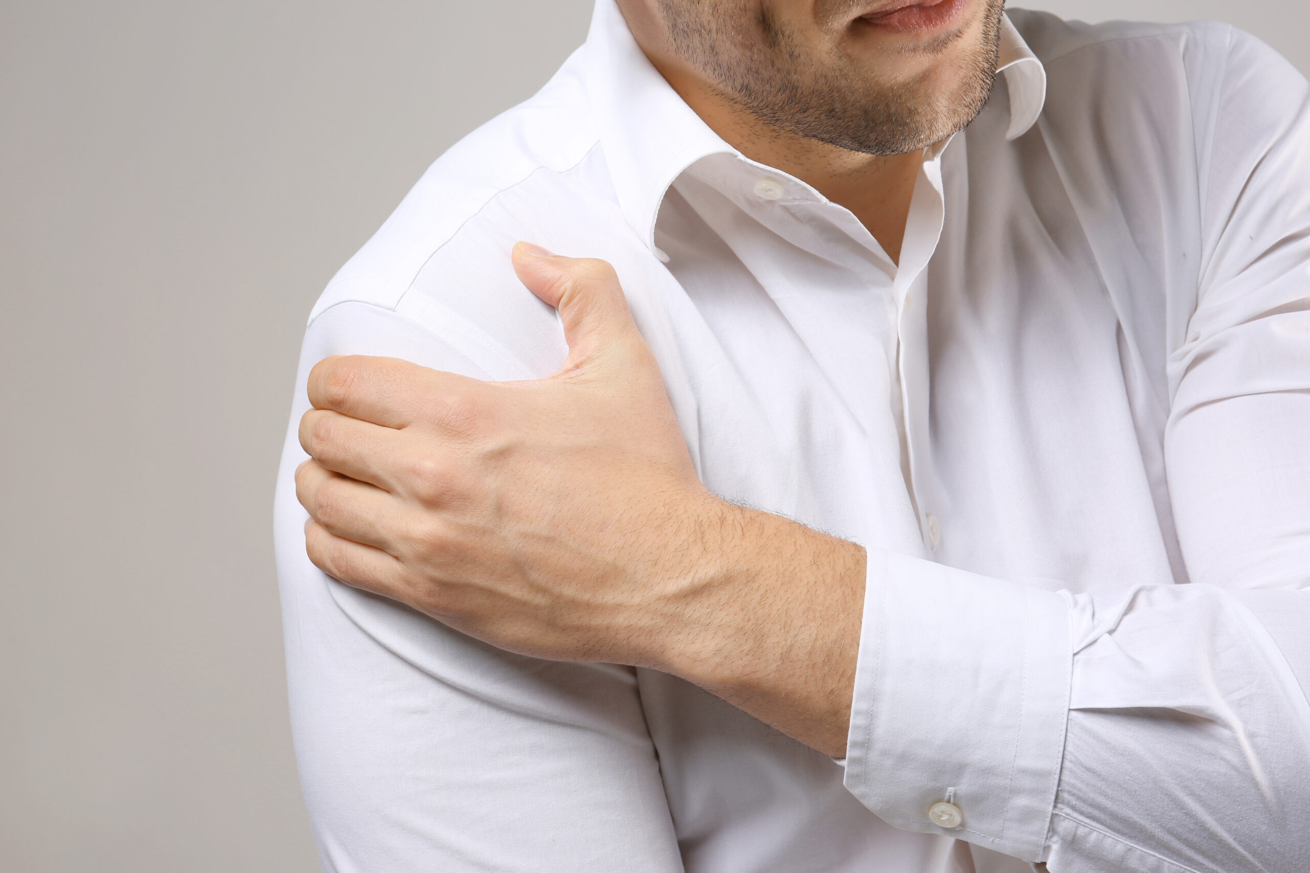 Young,Man,Suffering,From,Pain,In,Shoulder,,Closeup