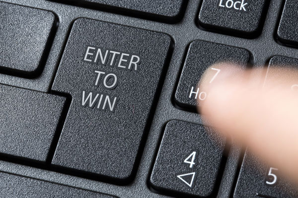 Finger getting ready to push a computer key that reads enter to win