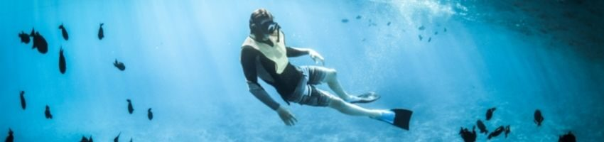 Snorkel expert enjoying his adventure at the bottom of sea with the little fishes around him