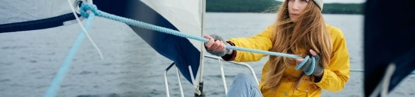 Young woman wearing yellow long sleeve trying to pull the rope in a small boat
