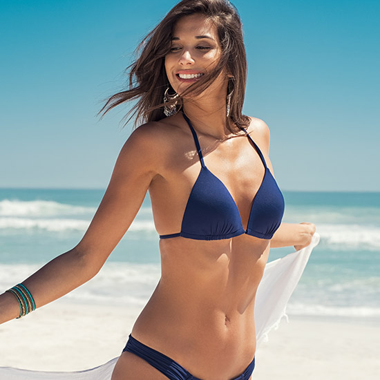 Woman smiling in blue bikini at beach Bellava MedAesthetics and Plastic Surgery Center in Bedford Hills, NY