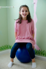 girl on sensory yoga ball
