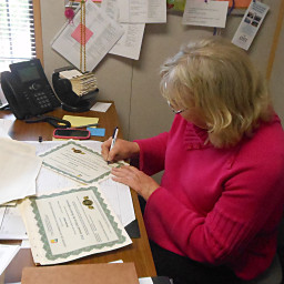 Suzanne signs Certificates for CMS training