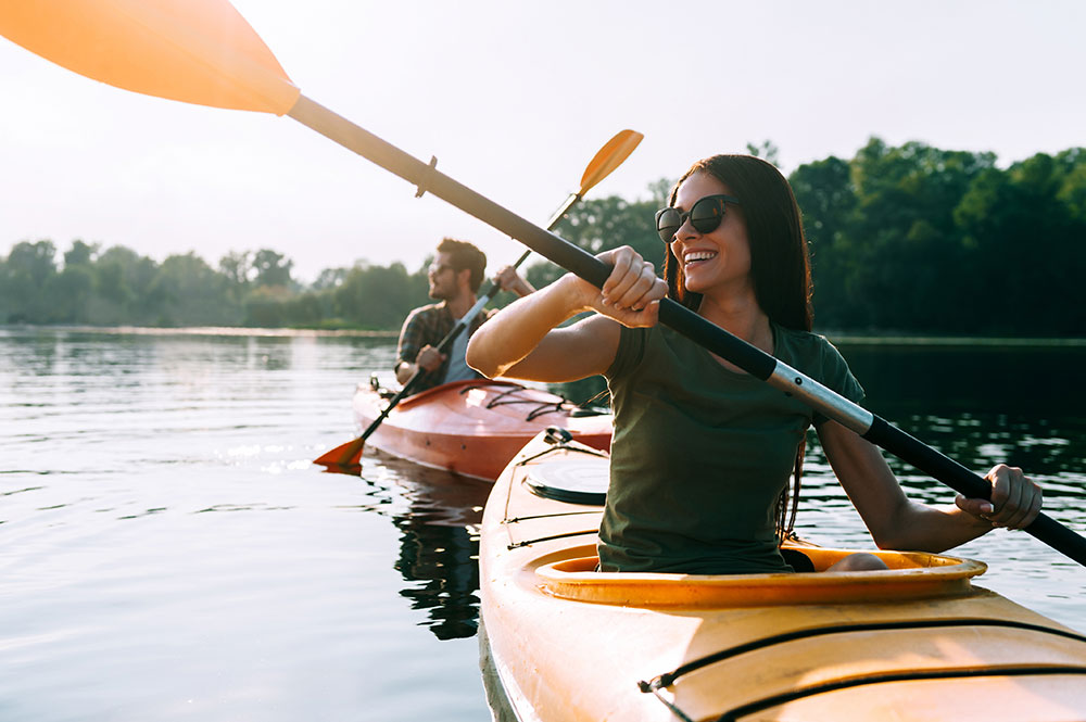 A man and woman kayaking on a lake