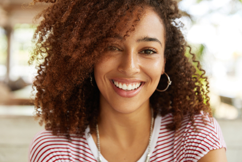 A young woman with curly hair smiling
