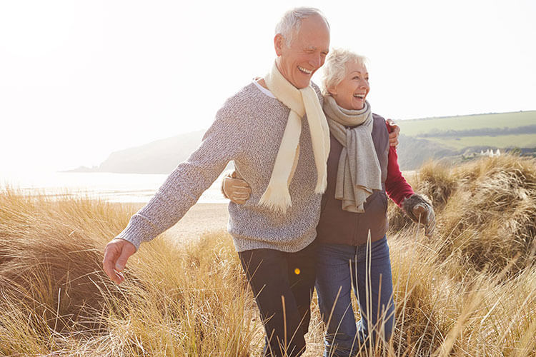 An older couple walking through a field with their arms around each other