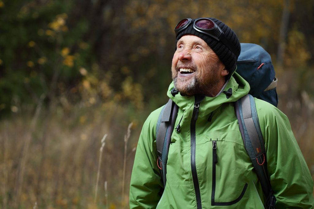 A man hiking in the woods and smiling