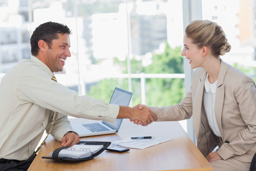 A woman at an interview shaking hands with an employer