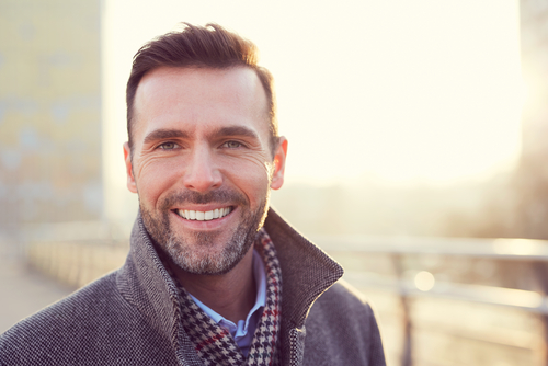 A middle aged man smiling outside with the sun shining behind him