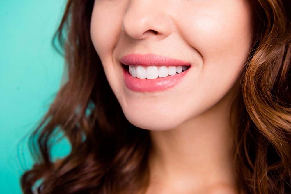 A close up of a woman's smile against a blue background
