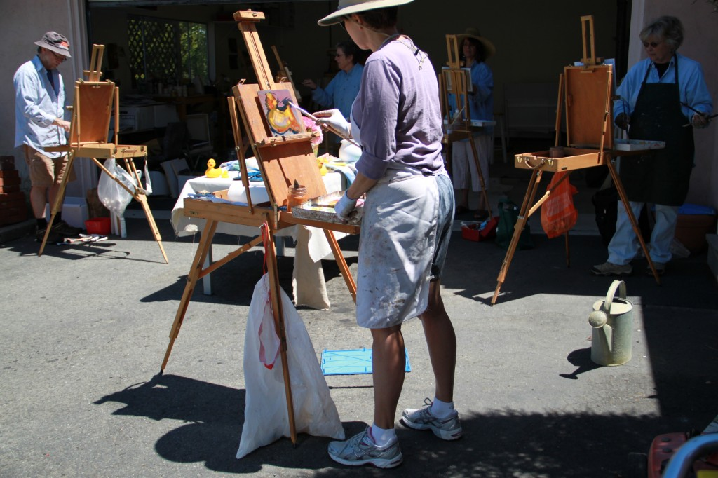 painters at easels in painting class outside in the sun