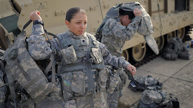 Spc. Karen Arvizu, left, puts on her hydration pack in preparation for her role as a volunteer in a physical demands study, Tuesday, Feb. 25, 2014, in Ft. Stewart, Ga. The Army is conducting a study that will determine how all soldiers, including women, for the first time, will be deemed fit to join its fighting units from infantry platoons to tank crews. (AP Photo/Stephen B. Morton)