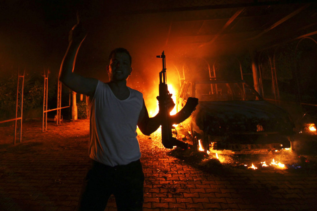 A protester reacts as the U.S. Consulate in Benghazi is seen in flames during a protest by an armed group said to have been protesting a film being produced in the United States in this September 11, 2012 file photo. Ahmed Abu Khatallah, a key suspect in the 2012 attack on the U.S. diplomatic compound in Benghazi, Libya, is being held on a U.S. ship following his capture over the weekend by U.S. special operations forces, a U.S. official said on June 17, 2014. The official, speaking on condition of anonymity, said the suspect was apprehended on the outskirts of Benghazi in a secret operation. He will be brought to the United States, the official added. REUTERS/Esam Al-Fetori/Files (LIBYA - Tags: POLITICS CIVIL UNREST)