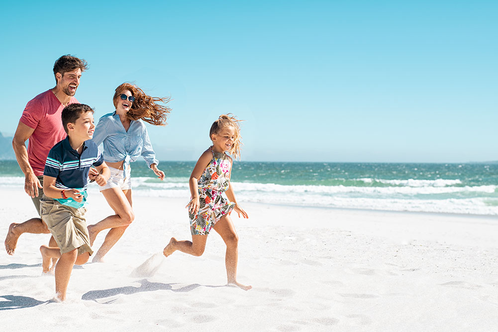 Happy Healthy Family Running on Beach