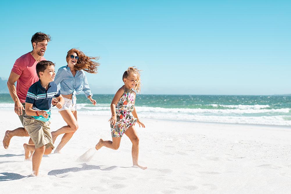 Happy Healthy Family Running on Beach