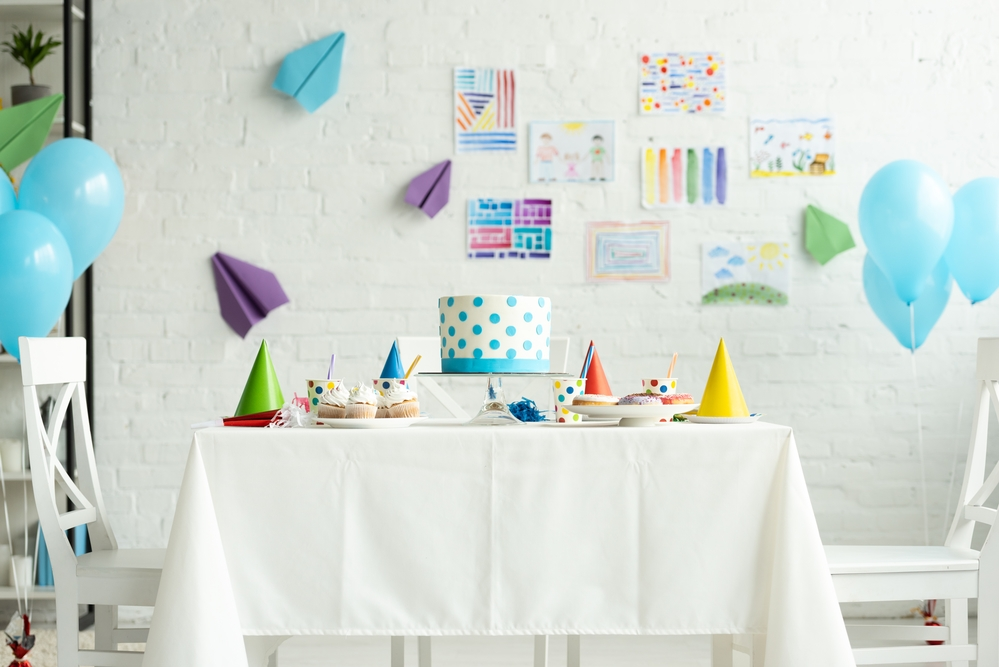 Festive cake on table in room decorated for birthday party