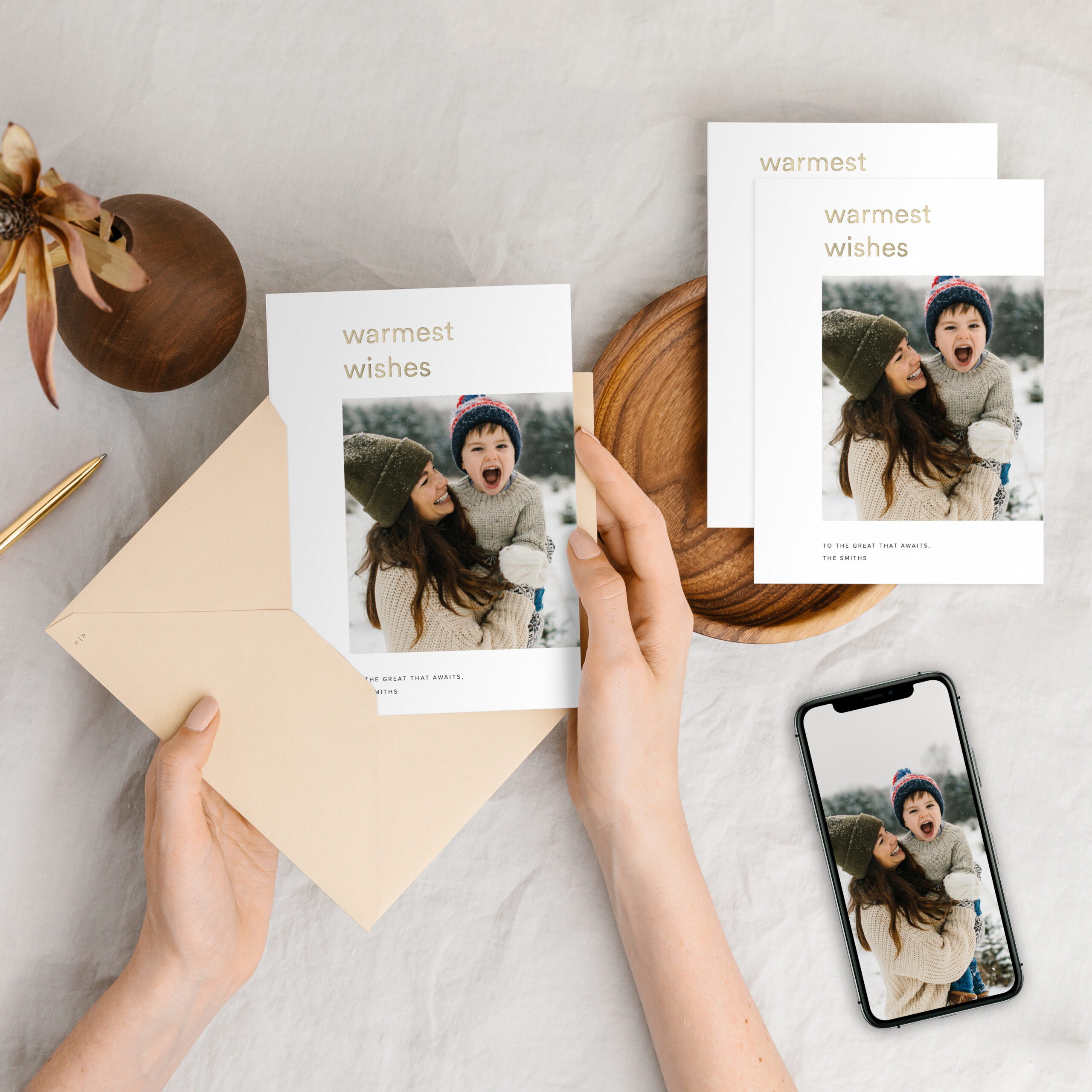 20191002-holiday-cards-hand-placing-in-gold-envelope-phone-photo-top-down-on-linen