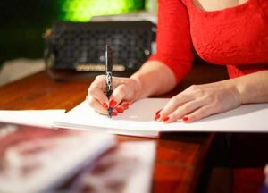 woman in red shirt signing book