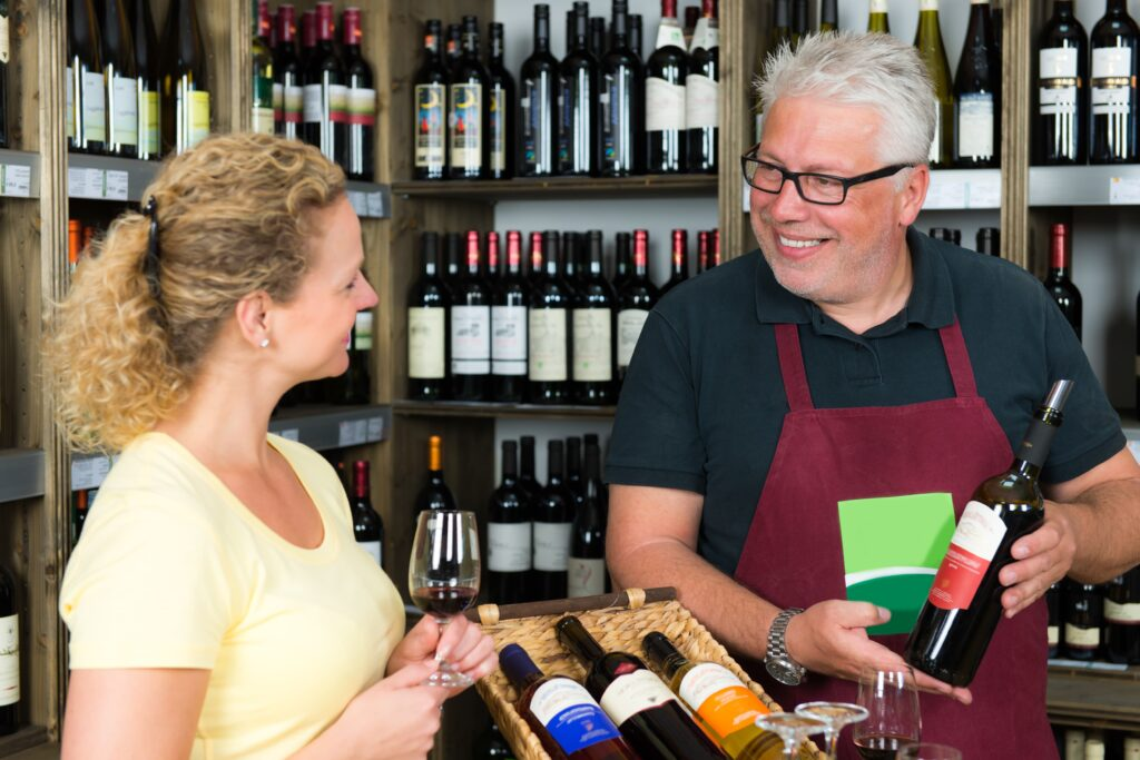 Wine Salesman Showing A Wine Bottle