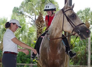 SUN PHOTO  Madison Schilling, 8, receives help from Olympian Kathleen Wightman-Raine.