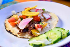 Flank steak taco with radishes, pico de gallo, and cucumbers on the side