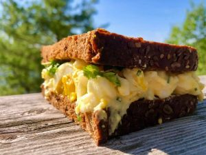 egg salad sandwich on dark rye with hard boiled egg tucked in