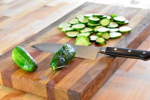 sliced cucumbers on cutting board with chef's knife