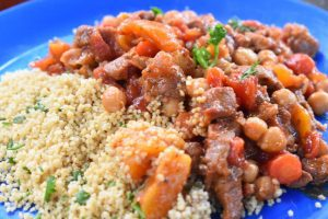 moroccan lamb stew and couscous on a blue camping plate