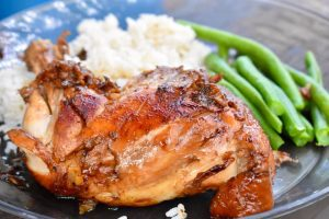 chicken adobo with beans and rice on plate