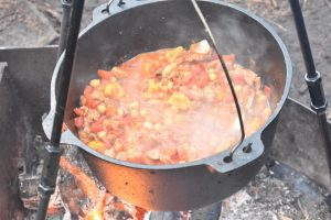 Dutch oven full of stew hanging on tripod over fire