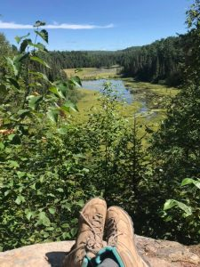 view overlooking beaver pond with crossed legs and hiking boots in shot