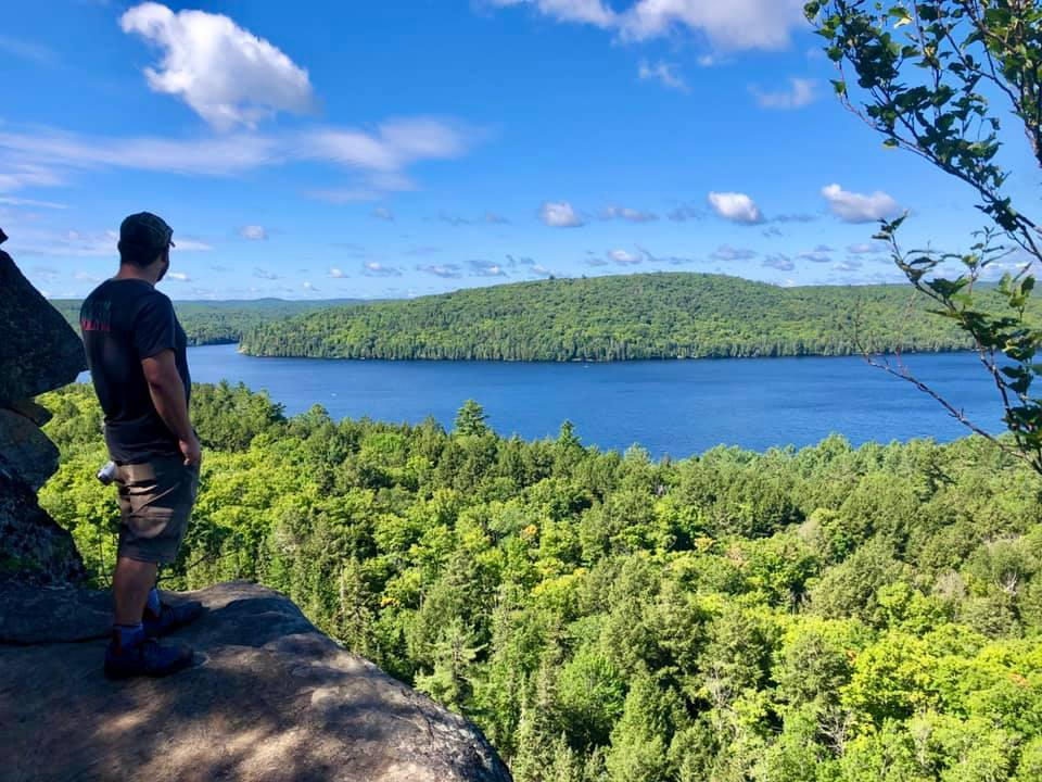 man overlooking a forest and river from a high rock