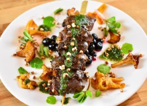 seared goose hearts on a skewer, surrounded by chanterelle mushrooms and green garnishes