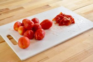 a pile of peeled tomatoes next to a pile of their skins