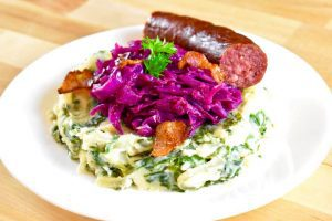 mashed potatoes mixed with green kale, with braised red cabbage and a smoked sausage on top
