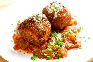two arancini balls in a bed of red tomato sauce and sprinkled with parmesan