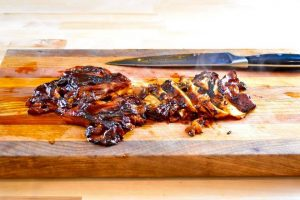 maitake mushroom slathered in barbecue sauce being cut on a cutting board