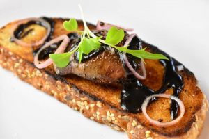 seared goose liver on toast with dark berry drizzle and shallot rings