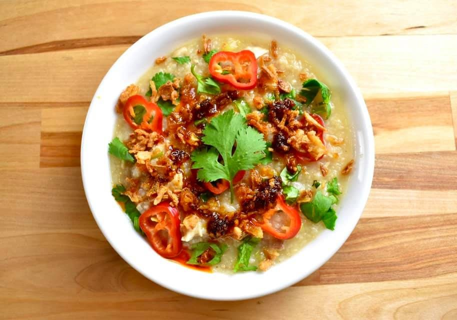 bowl of turkey congee topped with chili oil, red peppers, and cilantro