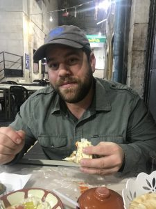 man eating bread at a table in Amman