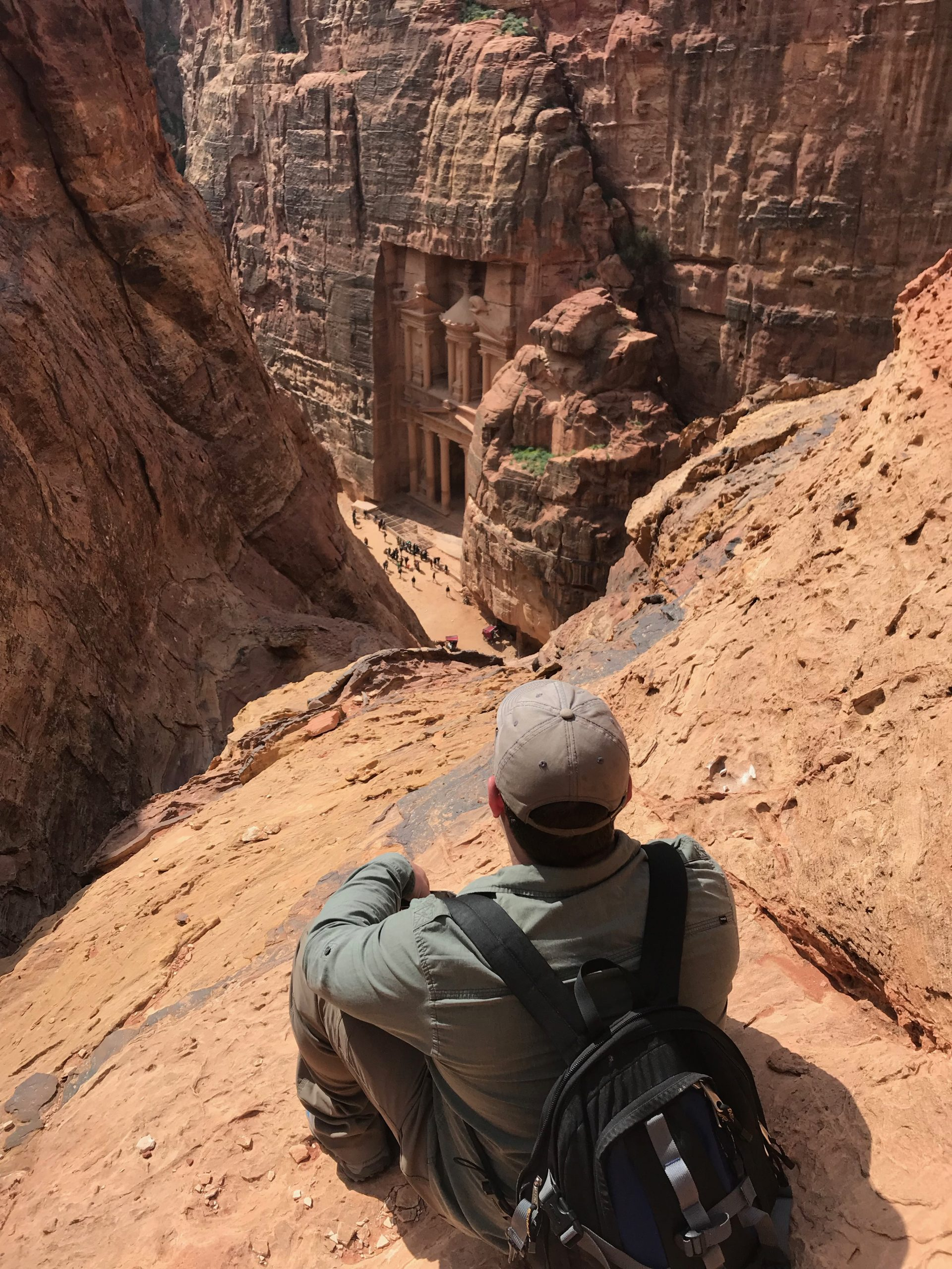 man crouching and looking down at the petra treasury, a building carved into a cliff face